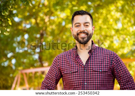 Portrait of a handsome Latin young man with a beard hanging out outdoors - stock photo