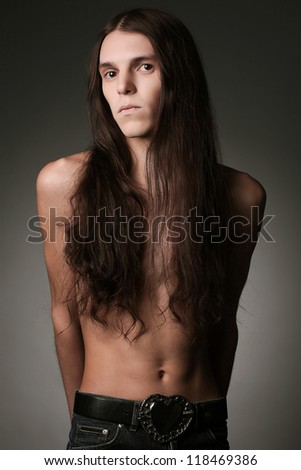 Portrait of a handsome long haired brunet male model over gray background. studio shot - stock photo