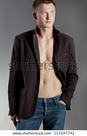 Portrait of a handsome macho man posing with his jacket unbuttoned to display his muscular torso and abdomen, hand in pocket - stock photo