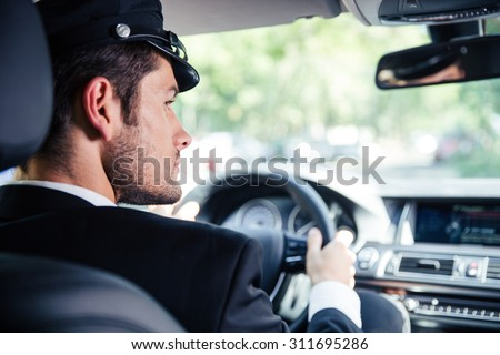Portrait of a handsome male chauffeur riding car - stock photo