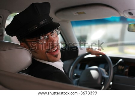 Portrait of a handsome male chauffeur sitting in a car talking to passenger.