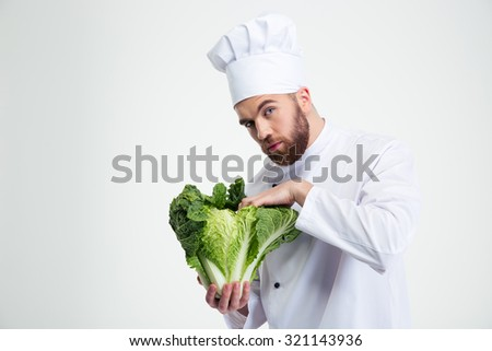 Portrait of a handsome male chef cook holding cabbage and looking at camera isolated on a white background - stock photo