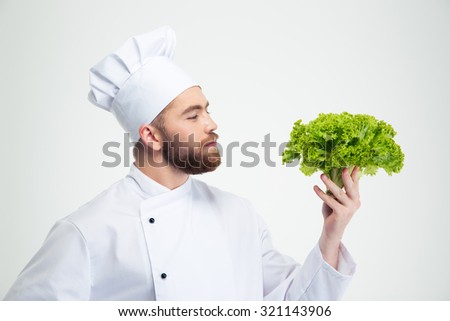 Portrait of a handsome male chef cook holding salad isolated on a white background - stock photo