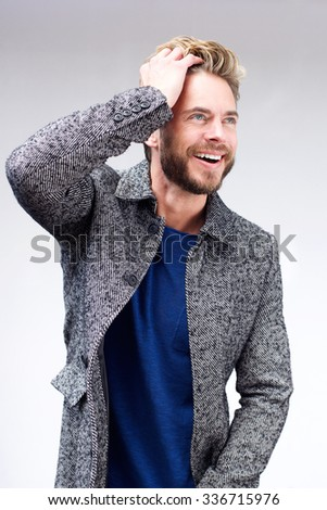 Portrait of a handsome male fashion model smiling with hand in hair
