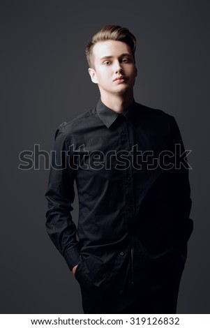 Portrait of a handsome male model in black clothes posing at studio. Men's beauty, fashion. - stock photo