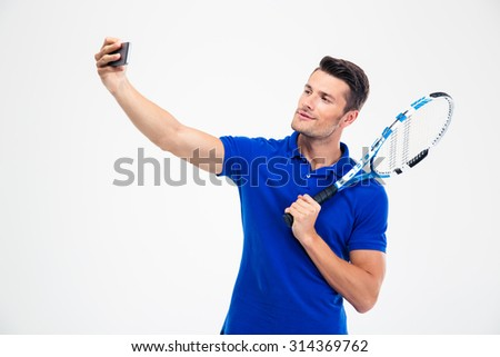 Portrait of a handsome male tennis player making selfie photo on smartphone isolated on a white background - stock photo