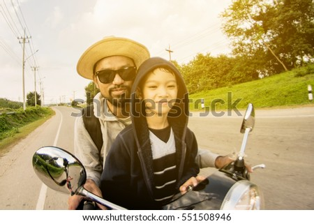 Portrait of a handsome man and son leaning on scooter outdoors
