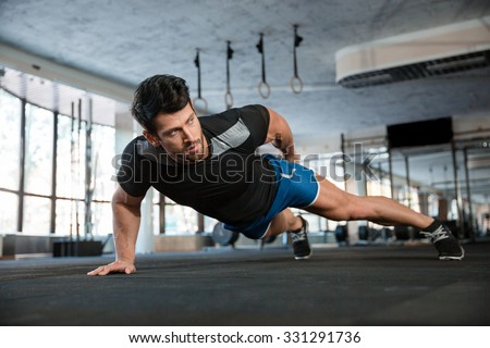 Portrait of a handsome man doing push ups exercise with one hand in fitness gym - stock photo