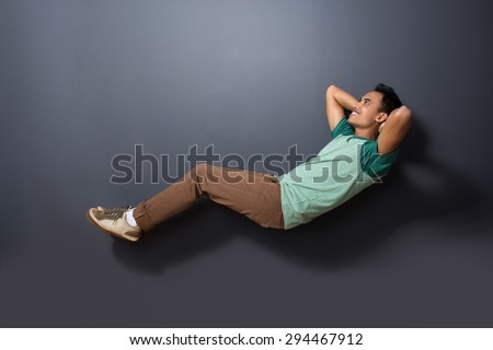 portrait of a handsome man floating with sleeping pose isolated on dark background - stock photo