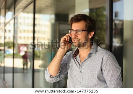 Portrait of a handsome man having phone conversation - stock photo