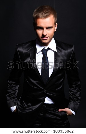 Portrait of a handsome man in a business suit on a black background - stock photo