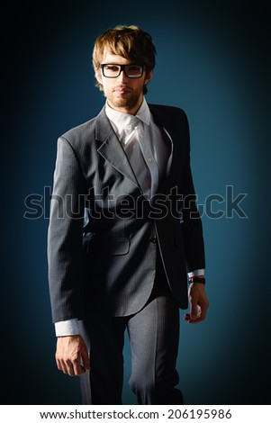 Portrait of a handsome man in elegant black suit and spectacles. Over dark background. - stock photo