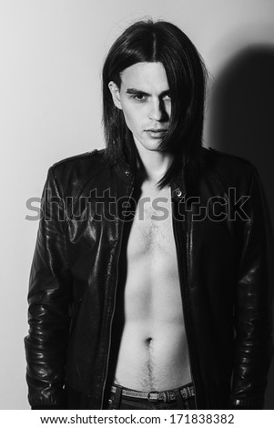 Portrait of a handsome man in studio, b & w photo, dressed in a leather jacket - stock photo