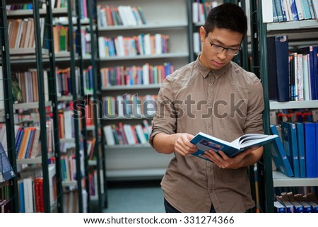 Portrait of a handsome man reading book in library - stock photo