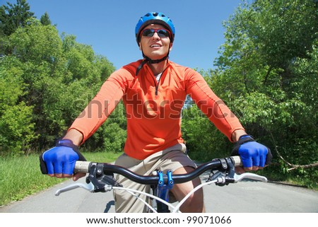 Portrait of a handsome man riding bike in park - stock photo