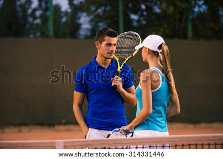 Portrait of a handsome man talking with her girlfriends at tennis court outdoors