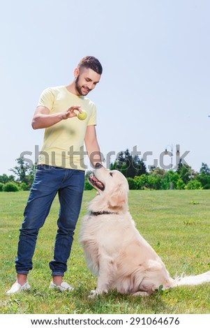 Portrait of a handsome man wearing yellow t-short and jeans with tattoo on his arm, standing holding a ball in his hand showing it to his lovely golden retriever sitting next to him in the park - stock photo