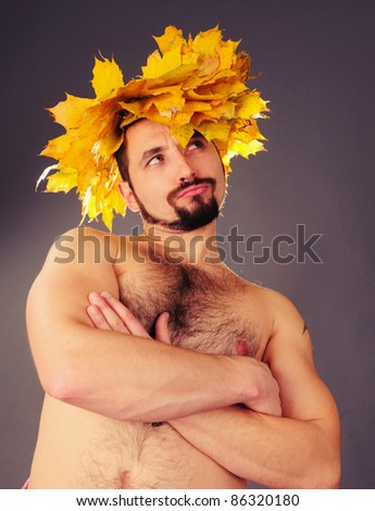 Portrait of a handsome man with a wreath of autumn leaves on the head.