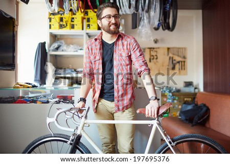 Portrait of a handsome man with bicycle in sports shop - stock photo