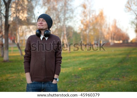 Portrait of a handsome man with earphones in the park