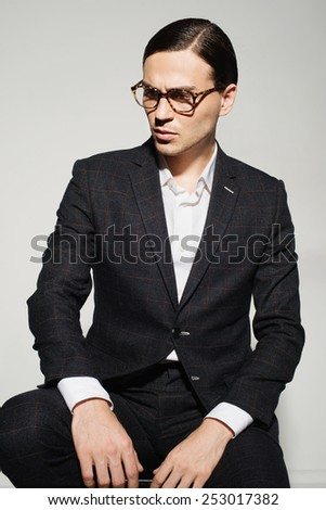 Portrait of a handsome man with glasses and a suit in the studio on a white background, concept of beauty and fashion - stock photo