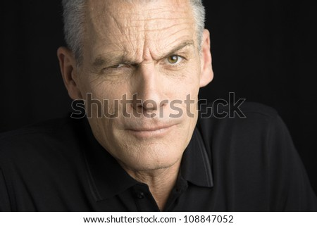 Portrait of a handsome man with grey hair raising one eyebrow