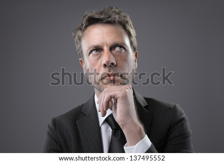 Portrait of a handsome mature business man thinking - stock photo