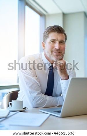 Portrait of a handsome mature businessman sitting at his desk, looking relaxed and confident and smiling lightly at the camera with his laptop open in front of him