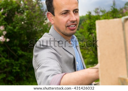 Portrait of a handsome middle-aged cheerful male artist on a trestle and easel painting during an art class - stock photo