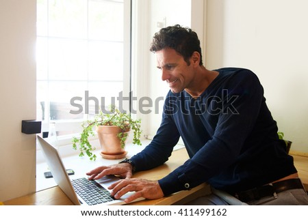 Portrait of a handsome middle aged man with laptop at home - stock photo
