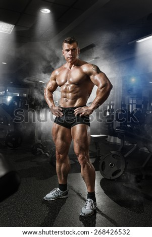 Portrait of a handsome muscular bodybuilder posing in gym