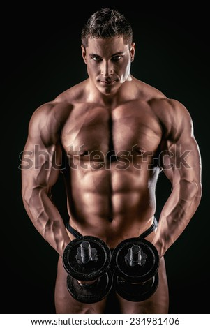 Portrait of a handsome muscular bodybuilder posing with dumbbells over black background.