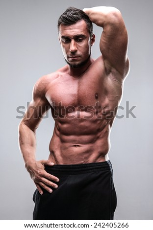Portrait of a handsome muscular man standing over gray background