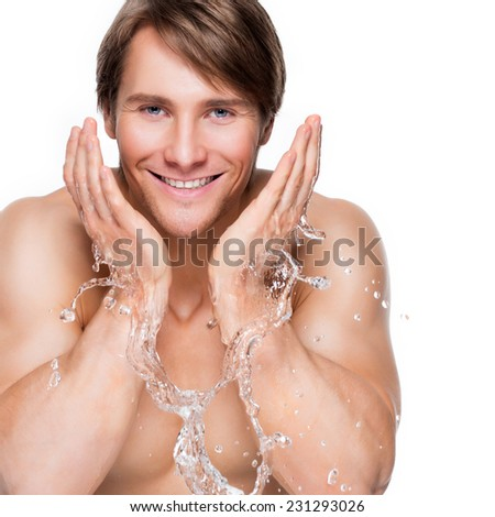 Portrait of a handsome smiling man washing his healthy face with water - isolated on white. - stock photo