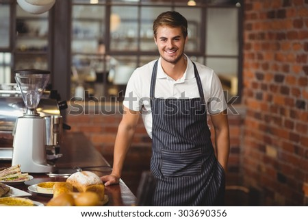 Portrait of a handsome waiter leaning on a food table at coffee shop - stock photo