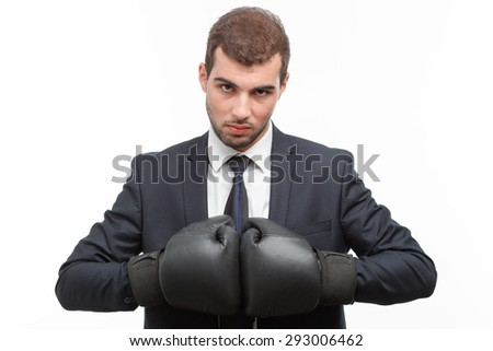 Portrait of a handsome young bearded man wearing a formal black suit and boxing gloves holding them together looking angry and aggressive, isolated on white background - stock photo
