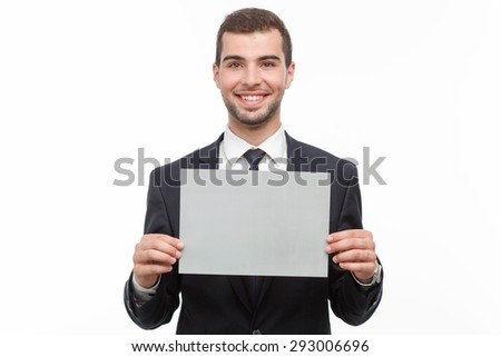 Portrait of a handsome young bearded man wearing a formal black suit and holding a copy space smiling, isolated on white background