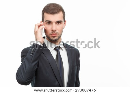 Portrait of a handsome young bearded man wearing a formal black suit and talking on his mobile phone looking very serious, isolated on white background - stock photo
