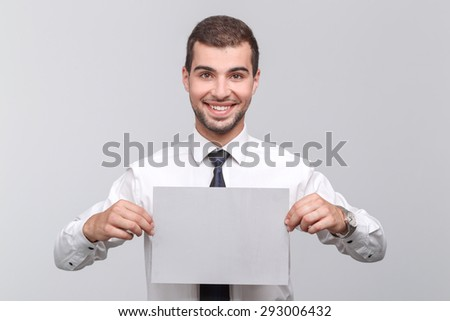 Portrait of a handsome young bearded man wearing white shirt and a tie holding a copy space smiling, isolated on grey background - stock photo