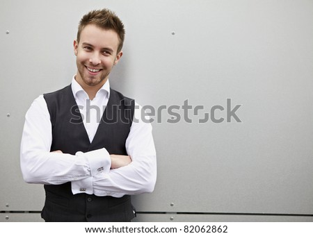 Portrait of a handsome young business man leaning against the metal wall. - stock photo