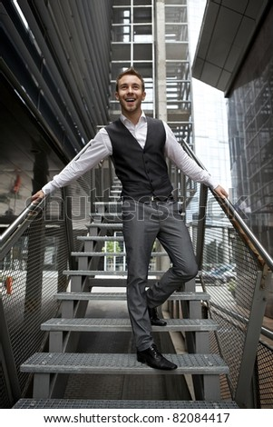 Portrait of a handsome young business man on a street ladder - stock photo
