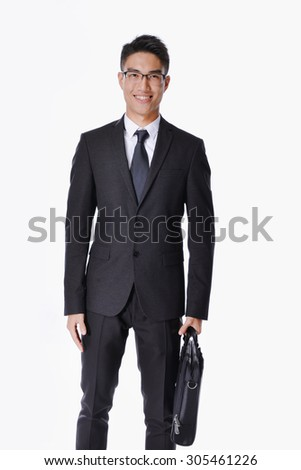 Portrait of a handsome young business man standing carrying a suitcase  - stock photo