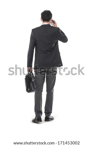 Portrait of a handsome young business man walking carrying a suitcase back �full body - stock photo