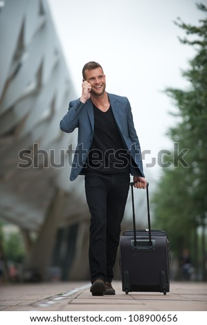 Portrait of a handsome young business man walking in the city phone and suitcase
