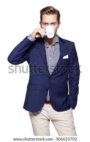 Portrait of a handsome young businessman drinking coffee. Isolated on white background. - stock photo