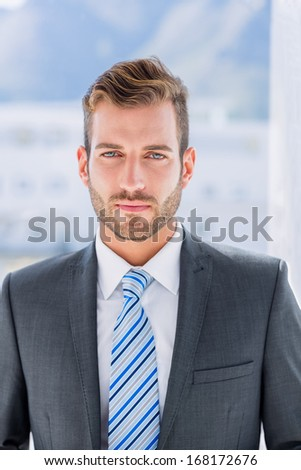 Portrait of a handsome young businessman over blurred background in office