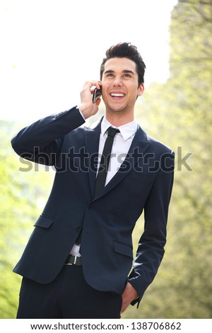 Portrait of a handsome young businessman talking on cellphone outdoors - stock photo