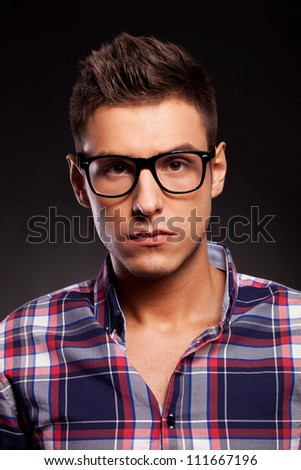 Portrait of a handsome young casual man with eyeglasses, looking into the camera, over black background - stock photo