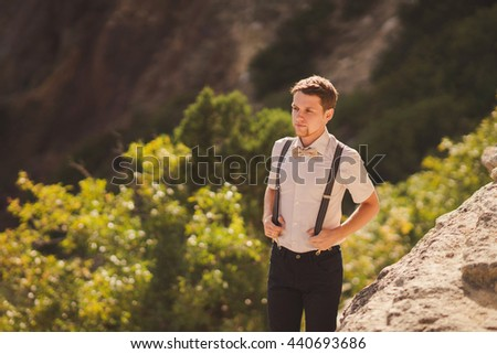 Portrait of a handsome young caucasian stylish man with beard standing on the background of beautiful nature, rock and trees, in sunlight - stock photo