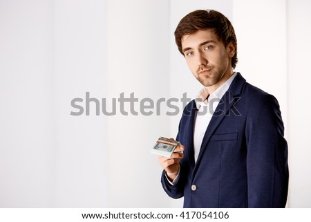 Portrait of a handsome young confident businessman in suit holding money looking at camera. - stock photo